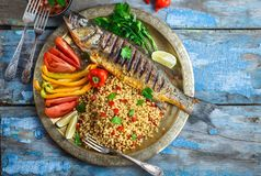 Grilled sea bass with ptitim and vegetables on copper plate, copy space.  royalty free stock image