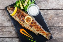 Grilled sea fish with lemon on stone slate background close up. Healthy food. Top view stock photography