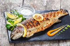 Grilled sea fish with lemon on stone slate background close up. Healthy food. Top view stock photo