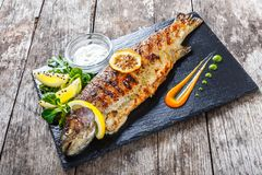 Grilled sea fish with lemon on stone slate background close up. Healthy food. Top view stock photos