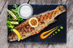 Grilled sea fish with lemon on stone slate background close up. Healthy food. Top view. Grilled sea fish with lemon on stone slate background close up. Healthy stock image