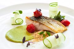 Grilled seabass with cherry tomatoes and avocado. Stock Photography