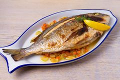 Grilled seabream on carrot, onion and celery stalks. Grilled seabream on carrot, onion and celery stalks Royalty Free Stock Images