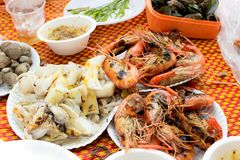 Grilled seafood. Grilled seafood squid, prawns, mussel, cockle with sauce on paper plate Royalty Free Stock Photo