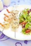 Grilled seafood on skewer and fresh salad Stock Images