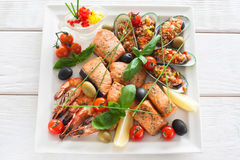 Grilled seafood variety on white plate with sauce Stock Photography