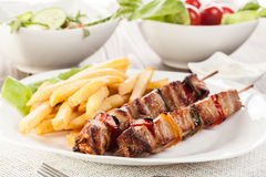 Grilled shashlik with chips Royalty Free Stock Photography