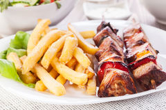 Grilled shashlik with chips Stock Images