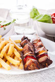 Grilled shashlik with chips Royalty Free Stock Images