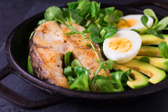 Grilled sheatfish fish steak with avocado, arugula and salad Stock Photos