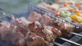 Grilled shish kebab on metal skewer. Chef hands cooking roasted meat barbecue with lots of smoke. BBQ fresh beef chop