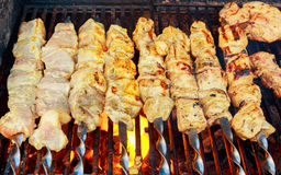 Grilled shish kebab on metal skewer. Chef hands cooking roasted meat barbecue with lots of smoke. Stock Photo