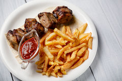 Grilled shish kebab served with french fries and sauce on white wooden table.  Royalty Free Stock Photos