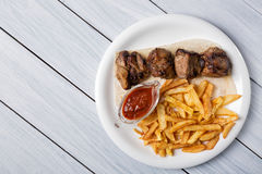 Grilled shish kebab served with french fries and sauce on white wooden table.  Stock Images