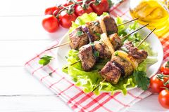 Grilled shish kebab or shashlik on white. Grilled shish kebab or shashlik on skewers  with salad leaves on white plate Stock Photo
