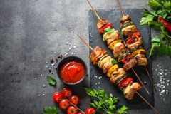 Grilled shish kebab with vegetables on black. Grilled shish kebab or shashlik with vegetables on black stone table. Pork meat. Barbeque meat dish. Top view copy royalty free stock photography