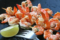 Grilled Shrimp. Skewers of grilled shrimp with lime and fork Stock Photography