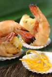Grilled Shrimp Appetizer. Two pieces of shrimp sitting in small sea shells on top of a banana leaf Royalty Free Stock Photography