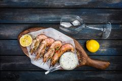 Grilled shrimp or langoustine with white sauce and half of a lemon. Grilled shrimp or langoustine with white sauce, half of a lemon and glass for the wine. On a Royalty Free Stock Photos