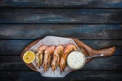 Grilled shrimp or langoustine with white sauce and lemon. Grilled shrimp or langoustine with white sauce, half of a lemon. On a wooden background. Top view Stock Photos