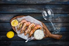 Grilled shrimp or langoustine with white sauce and lemon. Grilled shrimp or langoustine with white sauce, half of a lemon and glass for the wine. On a wooden Stock Image
