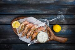 Grilled shrimp or langoustine with white sauce and lemon. royalty free stock image