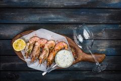 Grilled shrimp or langoustine with white sauce and lemon. stock image