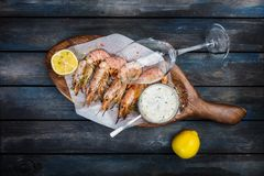 Grilled shrimp or langoustine with white sauce and lemon. stock photography