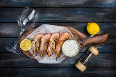 Grilled shrimp or langoustine with white sauce and lemon. royalty free stock images