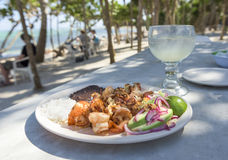 Grilled Shrimp Platter on Beach. A fresh platter of shrimp, grilled with garlic and butter with rice, beans, and avocado - on a beach covered with Palm Trees on Stock Photos