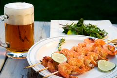 Grilled shrimps and beer. Grilled shrimps on wood sticks served with lime and mug of pale ale royalty free stock image