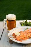 Grilled shrimps and beer outside. Grilled shrimps on wood sticks served on outside table with lime and mug of pale ale royalty free stock photo