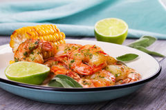 Grilled shrimps and corn garnished with lime and sage Royalty Free Stock Photography