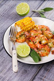 Grilled shrimps and corn garnished with lime and sage Stock Photo