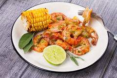 Grilled shrimps and corn garnished with lime and sage Royalty Free Stock Image
