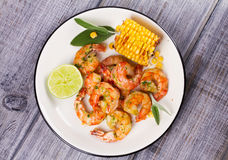 Grilled shrimps and corn garnished with lime and sage Stock Image