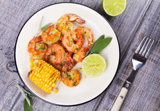 Grilled shrimps and corn garnished with lime and sage Stock Images