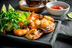 Grilled shrimps on a cutting Board with greens. On black rustic background stock image