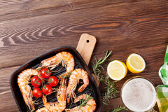 Grilled shrimps on frying pan and beer Royalty Free Stock Image