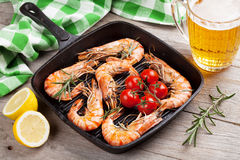 Grilled shrimps on frying pan and beer Stock Images