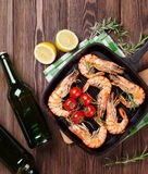 Grilled shrimps on frying pan and beer Royalty Free Stock Photo
