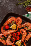 Grilled shrimps with lemon and rosemary on frying pan. Royalty Free Stock Images