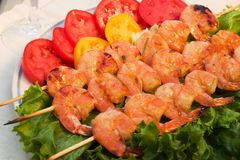 Grilled shrimps served. Grilled shrimps on wood sticks served with tomatos and green sald are ready to eat Stock Image