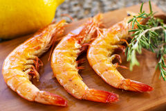 Grilled Shrimps Served on a Wooden Plate With Lemon and Rosemary. Three Grilled Seasoned Shrimps Closeup Royalty Free Stock Photo