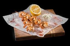 Grilled shrimps on skewers close-up of a blackboard. vertical, black background. Royalty Free Stock Image