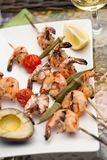 Grilled Shrimps Skewers for Dinner in Garden. Plate of grilled shrimps skewers with grilled vegetables and avocado. Served with lemon and lemon butter sauce Stock Photos