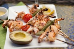 Grilled Shrimps Skewers for Dinner in Garden. Plate of grilled shrimps skewers with grilled vegetables and avocado. Served with lemon and lemon butter sauce Stock Photography