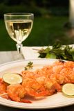 Grilled shrimps and white wine outdoor. Grilled shrimps on bamboo sticks served with limes, thyme twig and glass of white wine are served outside royalty free stock photo