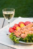 Grilled shrimps and white wine outdoor. Grilled shrimps on bamboo sticks served with limes, thyme twig and glass of white wine are served outside stock photo