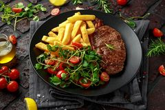 Grilled sirloin steak with potato fries and vegetables, tomato salad in a black plate. rustic table.  stock photos